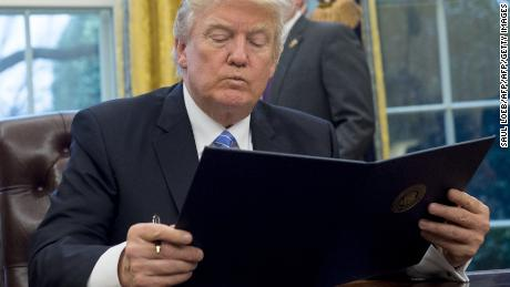 President Donald Trump reading the executive order withdrawing the US from the Trans-Pacific Partnership prior to signing it in the Oval Office on January 23, 2017.