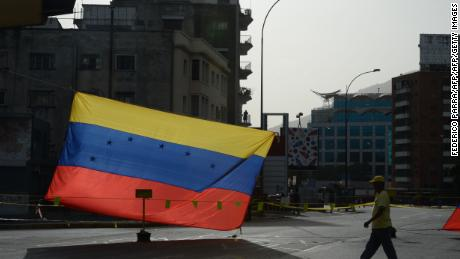 A man walks near a Venezuelan national flag in Caracas on July 10, 2017. Venezuela hit its 100th day of anti-government protests Sunday, amid uncertainty over whether the release from prison a day earlier of prominent political prisoner Leopoldo Lopez might open the way to negotiations to defuse the profound crisis gripping the country. / AFP PHOTO / Federico Parra        (Photo credit should read FEDERICO PARRA/AFP/Getty Images)