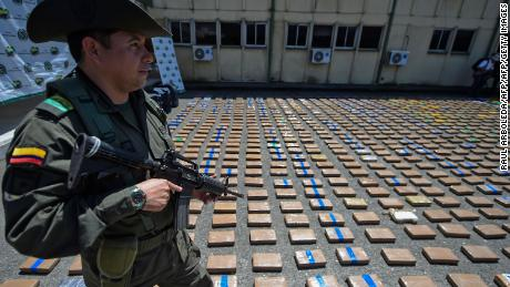 A member of the Colombian antinarcotics police, stands guard beside a one-ton shipment of cocaine seized to the country's biggest drug gang on August 10, 2017. (Credit :RAUL ARBOLEDA/AFP/Getty Images)
