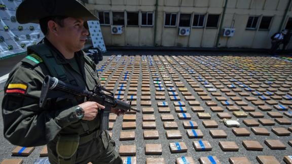 A member of the Colombian antinarcotics police, stands guard beside a one-ton shipment of cocaine seized to the country
