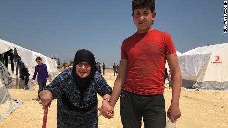 Fevziye, 68, is helped by a young man at a refugee camp in northern Syria.