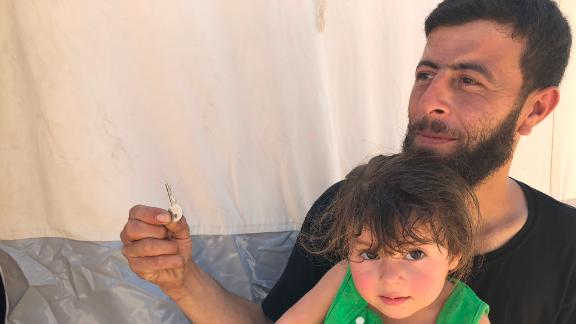"""Walid Dervish, 23, pictured with his daughter, says he brought his Douma house keys with him to the refugee camp. """"Maybe one day I can go back,"""" he said."""