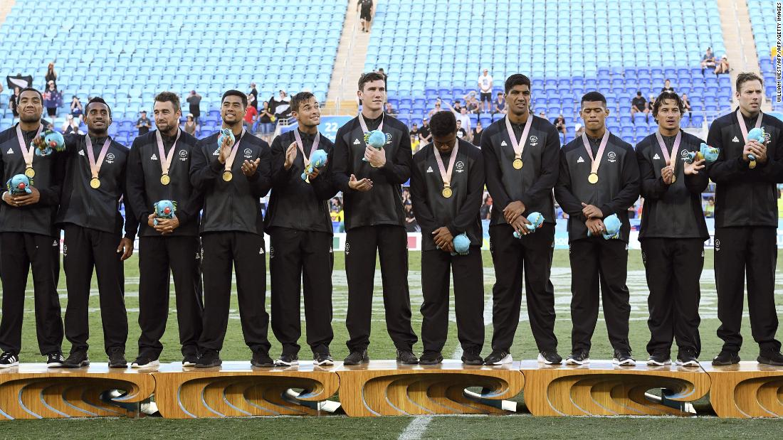 New Zealand players celebrate after defeating Fiji in the men's rugby sevens gold medal match at the Robina Stadium.