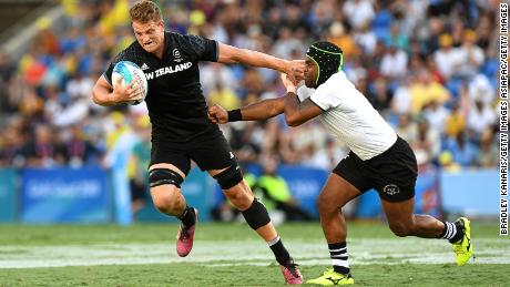 GOLD COAST, AUSTRALIA - APRIL 15: Scott Curry of New Zealand pushes away from the defence in the MenÕs Gold Medal Final match between Fiji and New Zealand during Rugby Sevens on day 11 of the Gold Coast 2018 Commonwealth Games at Robina Stadium on April 15, 2018 on the Gold Coast, Australia. (Photo by Bradley Kanaris/Getty Images)