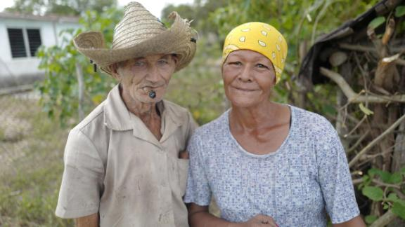 A couple in Céspedes, Cuba, pose in front of their home. After he took power in 1959, Fidel Castro promised to improve the lives of people living in Cuba's poverty-stricken countryside. He oversaw literacy and electrification campaigns and built hospitals for the rural poor. In recent decades, though, many Cubans living in the countryside have moved to cities, seeking better housing conditions and more economic opportunities.