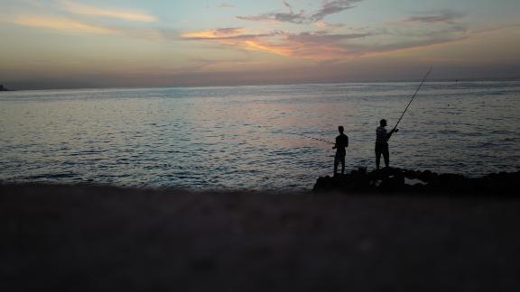 Cubans fish off Havana's Malecón seawall at sunset. The wall has been used during the years by Cubans launching small boats to attempt the dangerous journey across the Straits of Florida to the United Sta
