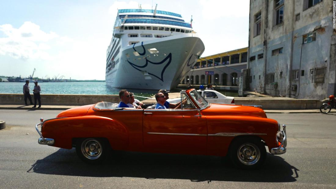 "A classic American car rolls by the first American cruise ship to visit Cuba in decades. In 2016 the US restarted regular cruise ship service to the island, and for the first time since the Cuban revolution, US visitors came to Cuba in large numbers. Americans are still restricted to ""permitted"" forms of travel to the island, and President Donald Trump has enacted restrictions on where Americans can stay and spend money, to prevent their dollars from going into the pocket of the Cuban military."