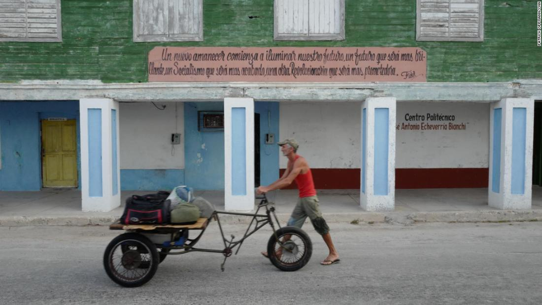 "A Cuban man wheels his possessions in Gibara, Cuba, under a sign quoting Fidel Castro:  ""A new dawn shall begin to illuminate our future, a future that shall be more brilliant, a Socialism that shall be more refined, a Revolutionary work that will be more promising."""