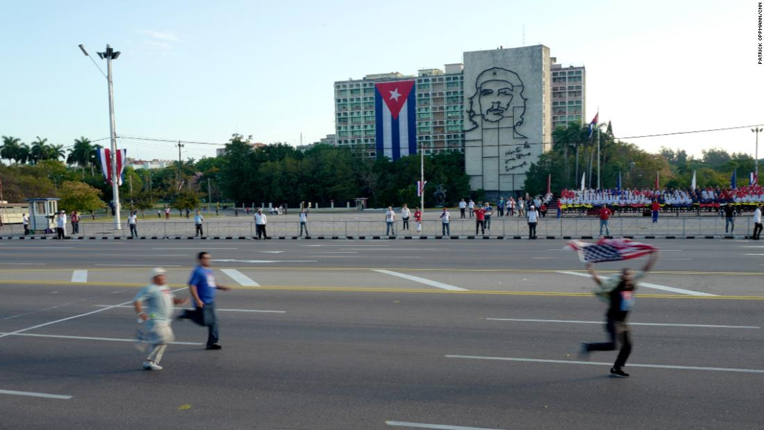 "A protester carrying an American flag runs through Havana's revolution square on May Day 2017 ahead of a government-sponsored parade as plainclothes Cuban security agents try to catch him. International human rights groups criticize the Cuban government for repressing internal dissent. Cuban officials say the island's dissidents are ""mercenaries"" paid by Washington to stir up trouble."