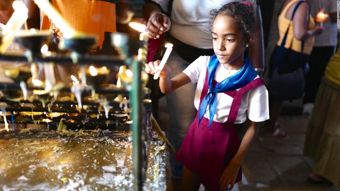 "A young Cuban girl in her ""pioneer"" school uniform lights a candle at a Havana church days before the 2015 visit of Pope Francis to Cuba. Religion was all but banned following the Cuban revolution, and Catholics in particular faced government discrimination for openly practicing their faith. Over the last 20 years, the Cuban government has slowly eased restrictions on religion. In 2015, Raul Castro, a longtime atheist, said meeting the Pope made him consider returning to the Catholic church."