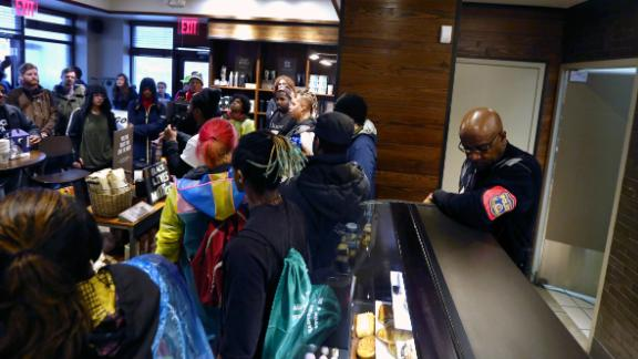 A plain-clothed police officer, right, mans a position behind the counter at the Starbucks that has become the center of protests Monday, April 16, 2018, in Philadelphia. The CEO of Starbucks arrived in Philadelphia hoping to meet with two black men who were arrested when the coffee chain