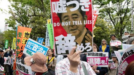 A protester holds a placard during a demonstration against Japan's Prime Minister Shinzo Abe on April 14, 2018.