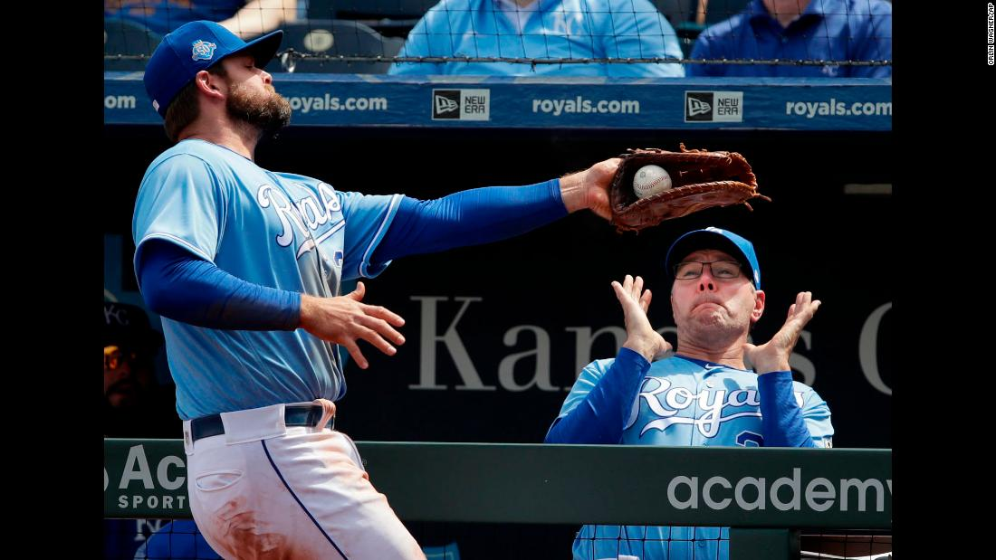 Kansas City Royals first baseman Lucas Duda, left, catches a foul ball where Kansas City Royals pitching coach Cal Eldred stands in the dugout during a baseball game against the Seattle Mariners on Wednesday, April 11, in Kansas City, Missouri.