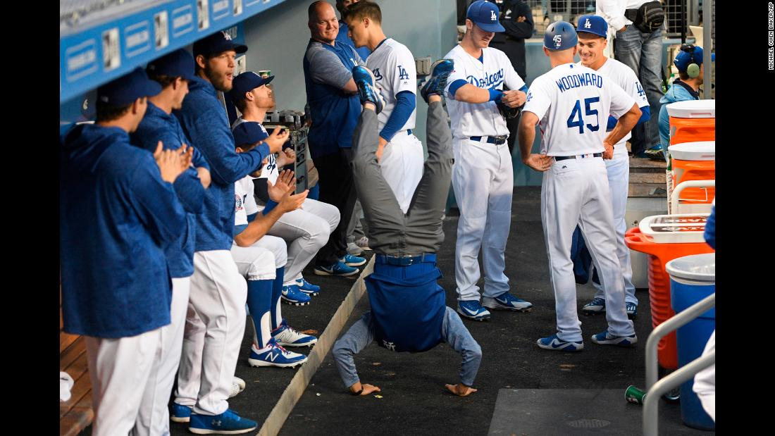 Will Ireton, the interpreter for Dodger pitcher Kenta Maeda, performs a handstand in the dugout before a baseball game against the Oakland Athletics on Wednesday, April 11, in Los Angeles.