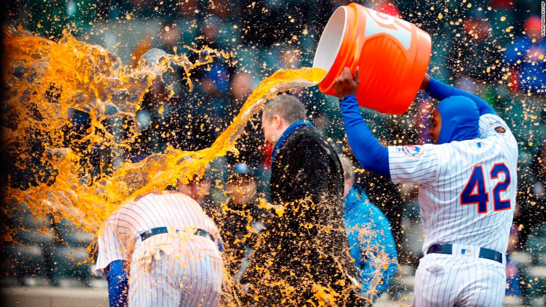 New York Mets left fielder Yoenis Cespedes, right, douses teammate Wilmer Flores after Flores hit a ninth-inning walk-off home run against the Milwaukee Brewers on Sunday, April 15, in New York.