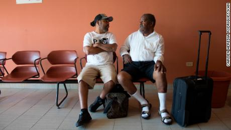 Since Hurricane Maria knocked out the Vieques hospital and dialysis center, Joe Garcia and Radamés Cabral Trinidad have had to seek lifesaving kidney treatments on Puerto Rico's main island. They must fly three times a week to this airport in Ceiba. The bags at their feet contain blankets, pillows and jackets to keep them comfortable during dialysis treatment. (Carmen Heredia Rodriguez/KHN)