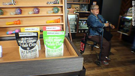 An older woman waits to check out, by the medical cannabis potato chips
