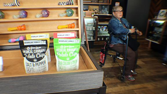 One woman waits to check out by a display of medical cannabis potato chips.
