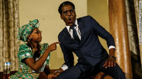 "Theatre actress Carol Magenga (L) interpreting Zimbabwe's former first lady Grace Mugabe and theatre actor Khetani Banda (R) in the role of former Zimbabwe's president Robert Mugabe perform on stage during a satirical play called ""Operation Restore Regasi"" at Theatre in the Park in Harare, March 29, 2018. The play, which chronicles the final days of former president Robert Mugabe's rule, marks an important watershed in Zimbabwe where satirical productions that mocked Mugabe were suppressed until very recently.  / AFP PHOTO / Jekesai NJIKIZANA        (Photo credit should read JEKESAI NJIKIZANA/AFP/Getty Images)"