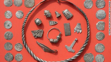 "Parts of the silver treasure are pictured on a table in Schaprode, northern Germany on April 13, 2018. A 13-year-old boy and a hobby archaeologist have unearthed a ""significant"" trove in Germany which may have belonged to the legendary Danish king Harald Bluetooth who brought Christianity to Denmark. A dig covering 400 square metres (4,300 square feet) that finally started over the weekend by the regional archaeology service has since uncovered a trove believed linked to the Danish king who reigned from around 958 to 986. Braided necklaces, pearls, brooches, a Thor's hammer, rings and up to 600 chipped coins were found, including more than 100 that date back to Bluetooth's era.  / AFP PHOTO / dpa / Stefan Sauer / Germany OUT        (Photo credit should read STEFAN SAUER/AFP/Getty Images)"