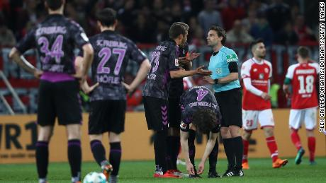 Freiburg players protest to referee Guido Winkmann after the controversial penalty decision.