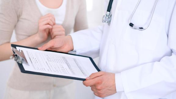 Close up of a male doctor holding an application form while consulting patient