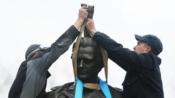 Parks Department workers place a harness over a statue of James Marion Sims as they prepare to take it down on Tuesday.