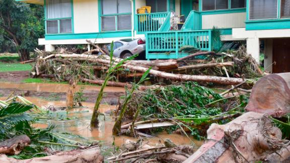 In this Sunday, morning, April 15, 2018 photo, a car is wedged between a house and debris in Anahola, Hawaii, after the Anahola River broke its banks in the pre-dawn hours and flooded the community downstream. (Dennis Fujimoto/The Garden Island via AP)