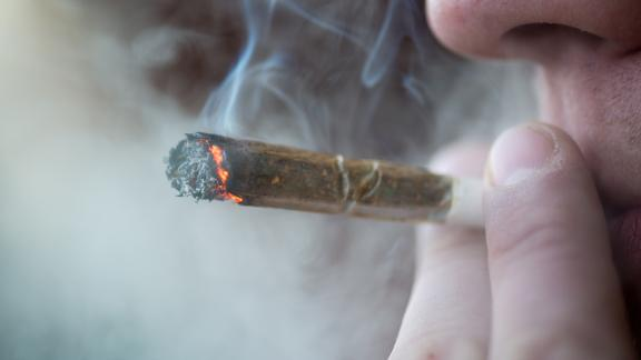 Man smoking marijuana cigarette soft drug in Amsterdam, Netherlands