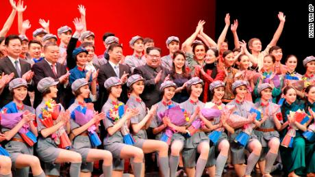North Korean leader Kim Jong Un, center, claps while posing with his wife Ri Sol Ju, government officials and members of a Chinese art troupe for a group photo at East Pyongyang Grand Theater in Pyongyang, North Korea.