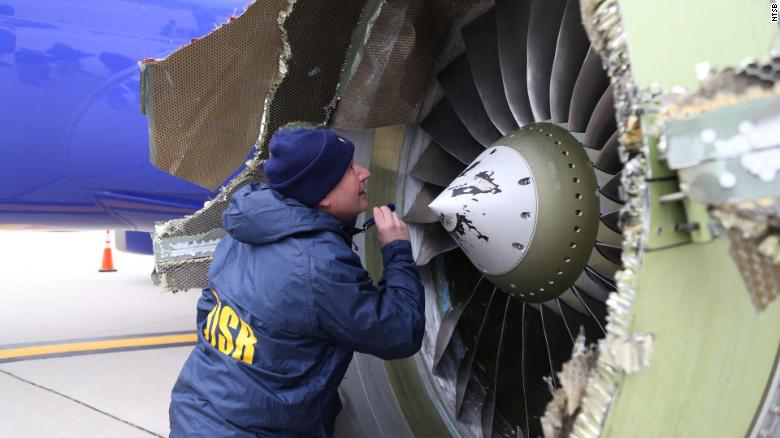 A National Transportation Safety Board investigator examines the damaged engine Tuesday.