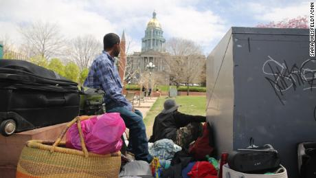 Homeless men look toward the Colorado state capitol in Civic Center Park, Denver. The rate of homelessness in Colorado has risen in recent years, despite falling national numbers.