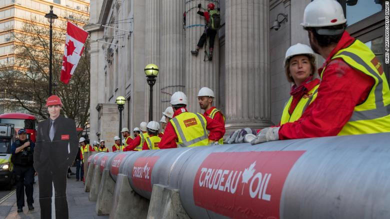 "Greenpeace activists build an ""oil pipeline"" next to a cutout of  Canadian Prime Minister Justin Trudeau."