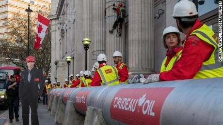 Greenpeace activists build a wood and card 'oil pipeline' next to a cardboard cut out of Justin Treudeau outside the Canadian High Commission, Canada House, to protest against the Trudeau government's plans to build an oil pipeline in British Columbia on April 18, 2018 in London, England.