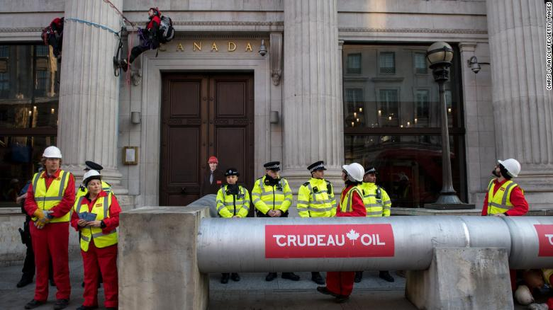 "Police stand guard as Greenpeace activists build an ""oil pipeline"" outside Canada House."