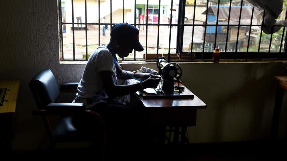 A victim of human trafficking in Libya sews clothes at Idia Renaissance non-governmental organisation in Benin, Edo State, midwest Nigeria, on October 21, 2016.