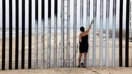 "Mexican-born artist Ana Teresa Fernandez created her mural ""Erasing the Border"" in 2011 by painting sections of the fence the same color as the sky, creating the illusion that it is missing"