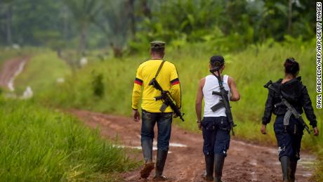 "Dissident guerrilla leader who goes by the name Aldemar (L), member of the First Front of the Revolutionary Armed Forces of Colombia (FARC), and other rebels, patrol the jungle along the Inirida River in Guaviare Department, Colombia, on September 26, 2017. Aldemar is one of several dissident guerrilla leaders who rejected a December peace deal that saw FARC rebels disarm after a half-century of war against the state. Like other dissidents, he is now a man wanted dead or alive by military patrols combing the jungle. FARC officially became a political party at a special congress in September 2017 but Aldemar says his jungle holdouts ""haven't changed an iota of our ideology."" / AFP PHOTO / Raul ARBOLEDA        (Photo credit should read RAUL ARBOLEDA/AFP/Getty Images)"
