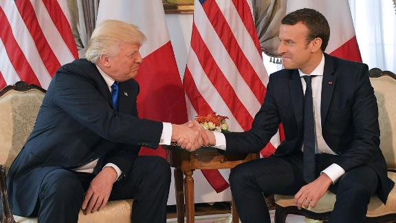 TOPSHOT - US President Donald Trump (L) and French President Emmanuel Macron (R) shake hands ahead of a working lunch, at the US ambassador's residence, on the sidelines of the NATO (North Atlantic Treaty Organization) summit, in Brussels, on May 25, 2017. / AFP PHOTO / Mandel NGAN        (Photo credit should read MANDEL NGAN/AFP/Getty Images)