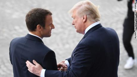 TOPSHOT - French President Emmanuel Macron (L) bids farewell to his US counterpart Donald Trump after the annual Bastille Day military parade on the Champs-Elysees avenue in Paris on July 14, 2017.