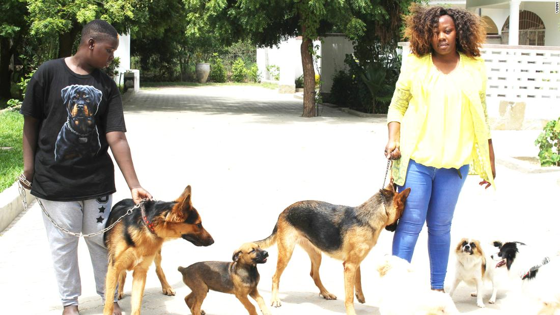 Phyllis Omido and her son, King David, stand with their dogs. Omido owns 10 dogs, five of which she trains as attack dogs.