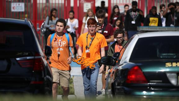 "Ryan Deitsch, right, a high school senior, carries a sign that reads ""love"" as he joins his fellow students from Marjory Stoneman Douglas High School, where 17 classmates and teachers were killed during a mass shooting in February, for the National School Walkout in Parkland, Florida."