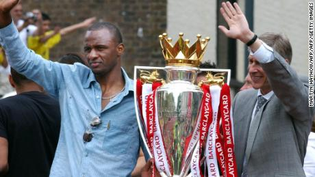LONDON, UNITED KINGDOM:  Arsenal team captain Patrick Vieira (L) and manager Arsene Wenger wave from the open-top bus carrying the winners of the British Premier League Championship, Arsenal players and their families, on  its way to Islington Town Hall,16 May  2004, as part of the Club's victory celebration.       AFP PHOTO/ Martyn HAYHOW  (Photo credit should read MARTYN HAYHOW/AFP/Getty Images)