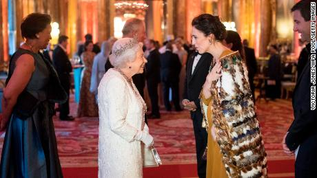 Queen Elizabeth II greets Jacinda Ardern in the Blue Drawing Room at The Queen's Dinner on April 19 in London.