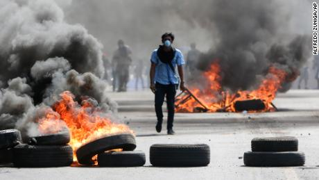 A masked protester walks between burning barricades Friday in Managua, Nicaragua.