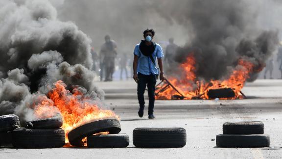 A masked protester walks between burning barricades Friday in Managua, Nicaragua.