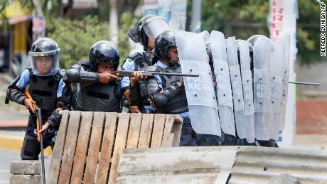 A police officer aims his weapon at students protesting social security reforms  in Managua, Nicaragua.