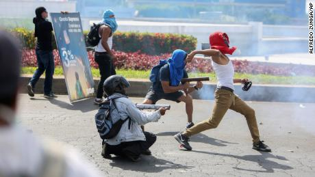 Masked protesters fire from a homemade mortars at riot police as another winds up to throw a rock during a third day of violent clashes in Managua, Nicaragua, Friday, April 20, 2018. The clashes, pitting protesters opposed to social security reforms against riot police and pro-government groups, have rocked the capital, and a half-dozen other cities over the last three days. The Organization of American States have expressed concern over the heavy-handed crackdown, while also calling on demonstrators to protest peacefully. (AP Photo/Alfredo Zuniga)