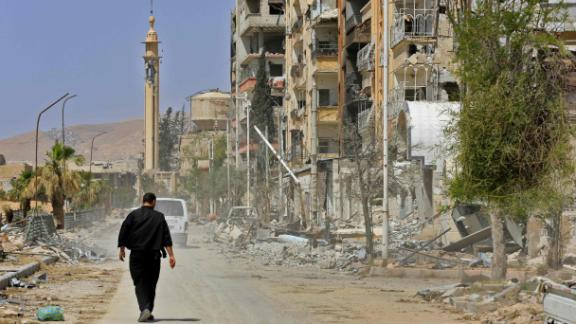 A picture taken during a Syrian army-organised tour on April 20, 2018 shows a man walking down a street past destruction in the Eastern Ghouta town of Douma on the outskirts of the capital Damascus.