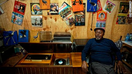 "In this photo taken Thursday, March 1, 2018, James ""Jimmy"" Rugami recounts his story inside his vinyl records stall in Kenyatta Market in Nairobi, Kenya. Tucked into a busy market in Kenya's capital is ""Real Vinyl Guru"", arguably the last record store still in operation in the country and which now enjoys the growing interest of music lovers who want to look beyond sleek digital offerings and return to the pleasure of browsing for a classic find. (AP Photo/Ben Curtis)"